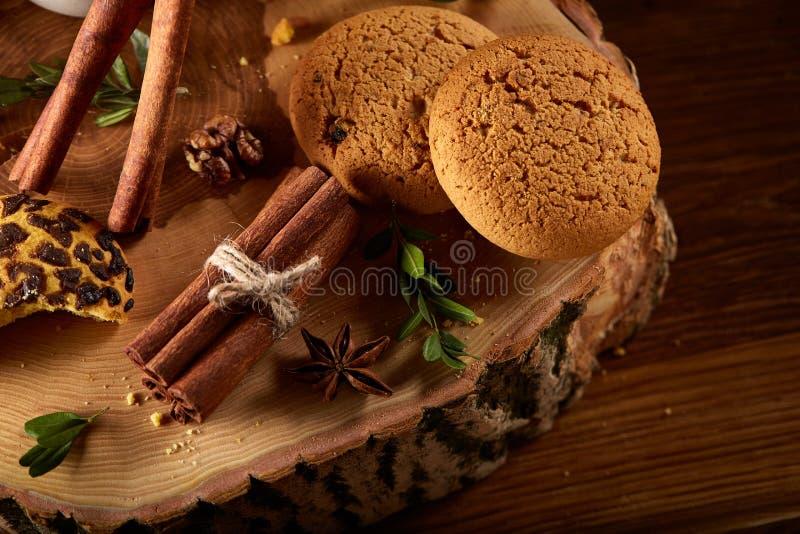 Natura morta di Natale con l'assortimento dei biscotti, della cannella e delle arance secche su un ceppo, primo piano, fuoco sele fotografie stock libere da diritti