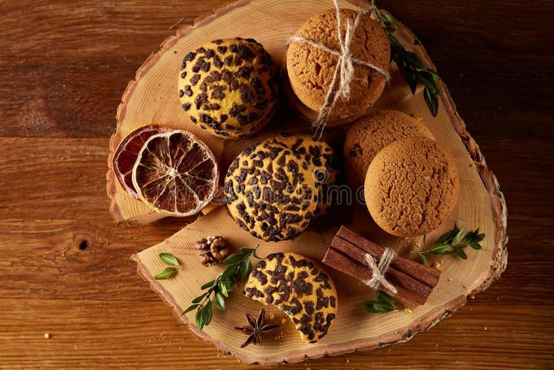 Natura morta di Natale con l'assortimento dei biscotti, della cannella e delle arance secche su un ceppo, primo piano, fuoco sele immagine stock libera da diritti