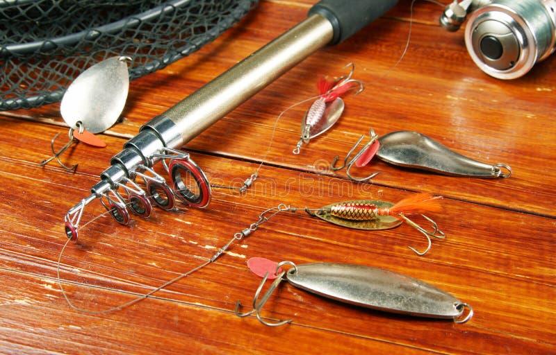 Natura morta di pesca con le varie esche e la filatura del metallo immagine stock