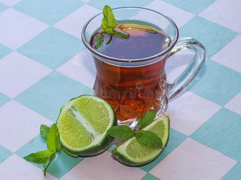 Natura morta di tè nero in tazza di vetro, foglie di menta e calce sui precedenti della tavola fotografia stock