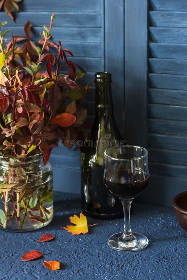 Natura morta di umore di autunno con un mazzo delle foglie di autunno e di un vetro di vino rosso fotografia stock