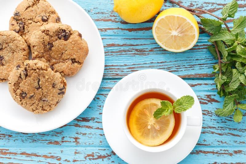 Natura morta fresca del rinfresco di estate dei biscotti di uva passa della bevanda della menta del tè del limone immagine stock