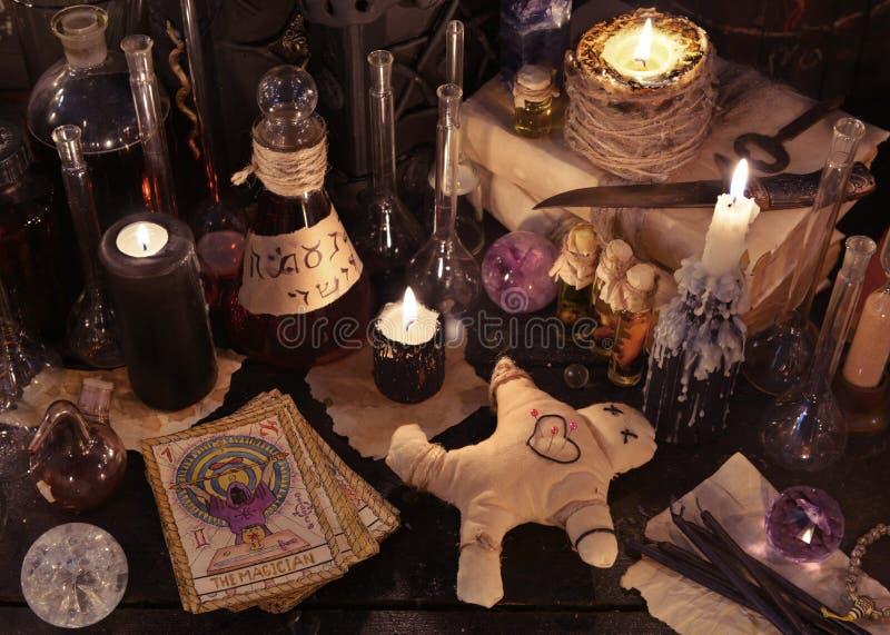 Natura morta mistica con la bambola di voodoo, le carte di tarocchi, i libri della strega e gli oggetti magici immagini stock libere da diritti