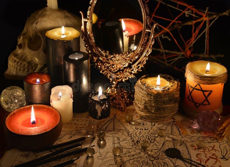 Natura morta mistica con lo specchio, la carta del demone e le candele magici fotografie stock libere da diritti
