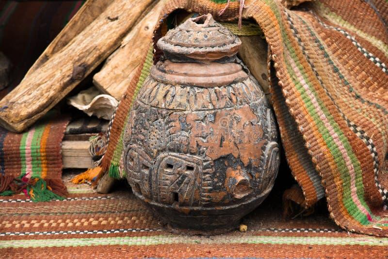 Natura morta orientale con i tappeti orientali etnici degli ornamenti e un vecchio vaso ceramico tagliato immagini stock