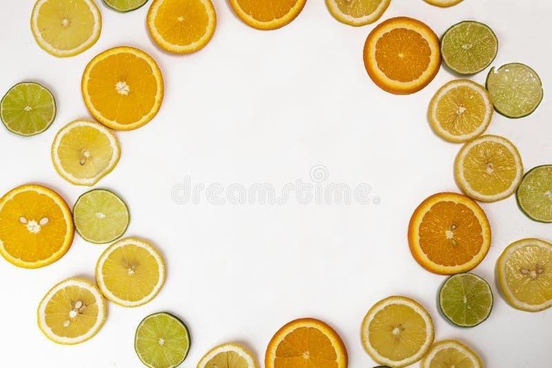 Natura morta piana di disposizione con la corona dall'agrume: frutta arancio; calce; immagini stock