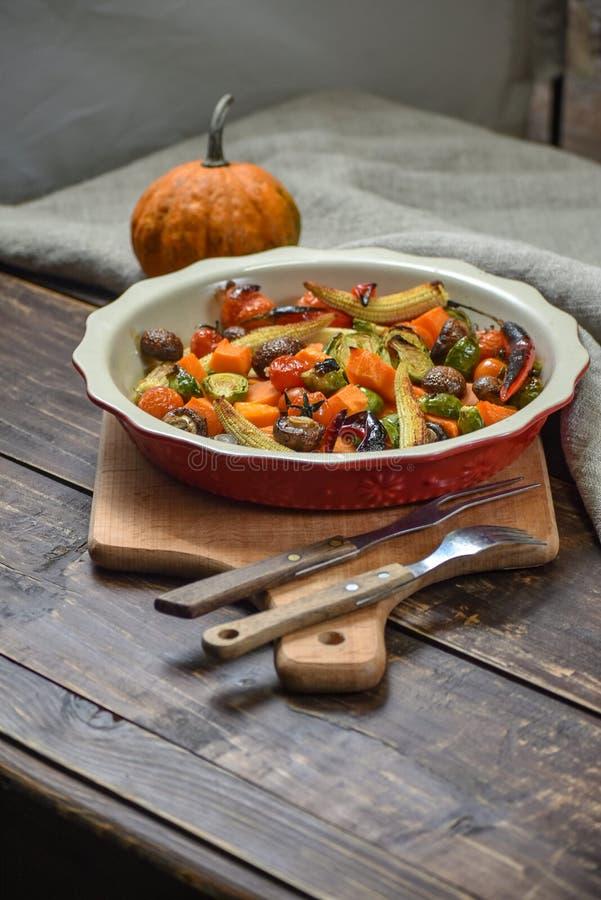 Natura morta rurale delle verdure arrostite ed in un grande piatto ceramico ed in apparecchi su un fondo di legno Copi lo spazio fotografie stock