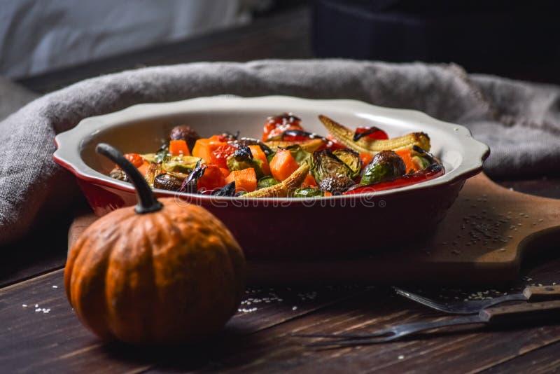Natura morta rurale delle verdure arrostite ed in un grande piatto ceramico ed in apparecchi su un fondo di legno Copi lo spazio immagini stock