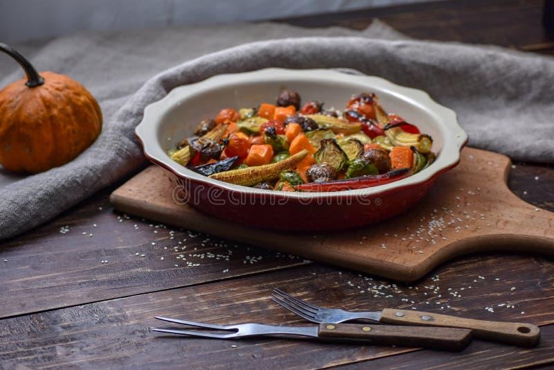 Natura morta rurale delle verdure arrostite ed in un grande piatto ceramico ed in apparecchi su un fondo di legno Copi lo spazio immagine stock libera da diritti