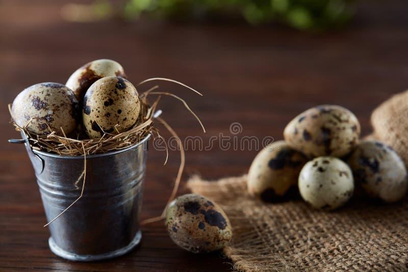 Natura morta rustica con le uova di quaglia in secchio, scatola e ciotola su un tovagliolo di tela sopra fondo di legno, fuoco se immagini stock libere da diritti