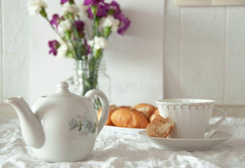 Natura morta rustica della prima colazione di mattina Croissant della tazza di tè con crema, fiori in vaso Luce soleggiata rurale immagini stock libere da diritti