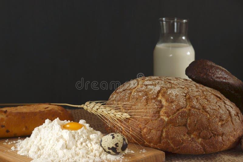 Natura morta rustica di stile con pane, l'uovo, il latte e una collina della farina di frumento immagini stock