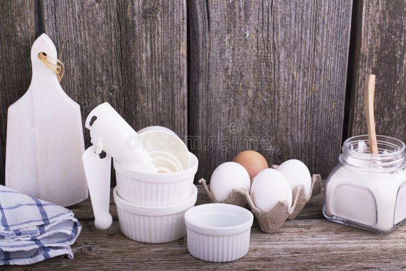 Natura morta su una tavola di legno della cucina con le muffe ceramiche bianche per cuocere, le uova, la farina ed altri utensili immagini stock