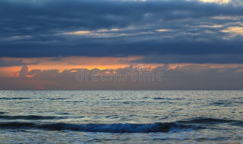 Natura nel periodo crepuscolare che inclusione dell'alba sopra il mare Spiaggia di estate con acqua blu ed il cielo porpora al tr fotografia stock libera da diritti