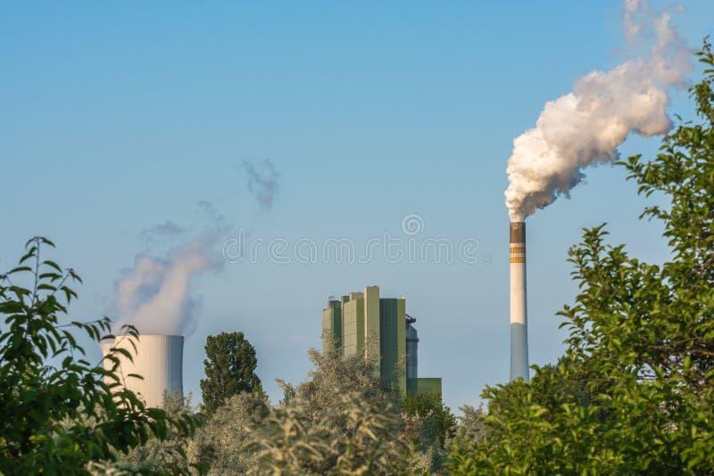 Natura sotto l'influenza della centrale elettrica vicina con il camino molto fumoso immagini stock libere da diritti