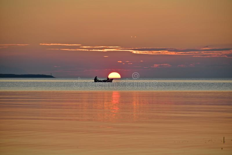 Natural abstract background, The sun is setting and evening is falling as hope rises. Sunset over the sea,works and days, red sunset over water with the stock photos