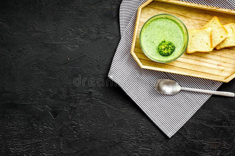Natural, alimento biológico Sopa-puré vegetal verde en preparado del cuenco servido con los bizcochos tostados en copia negra de  fotografía de archivo libre de regalías