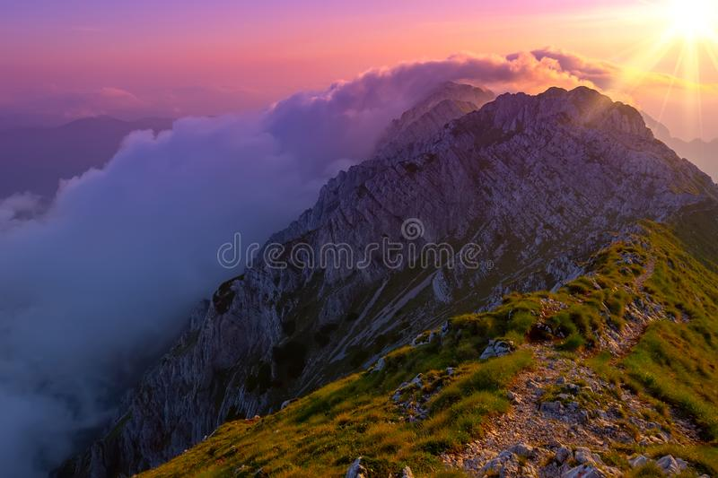 Natural alpine scenery landscape of mountains and dramatic strong sun that rises and shines over cliffs and peaks. Breathtaking royalty free stock photography