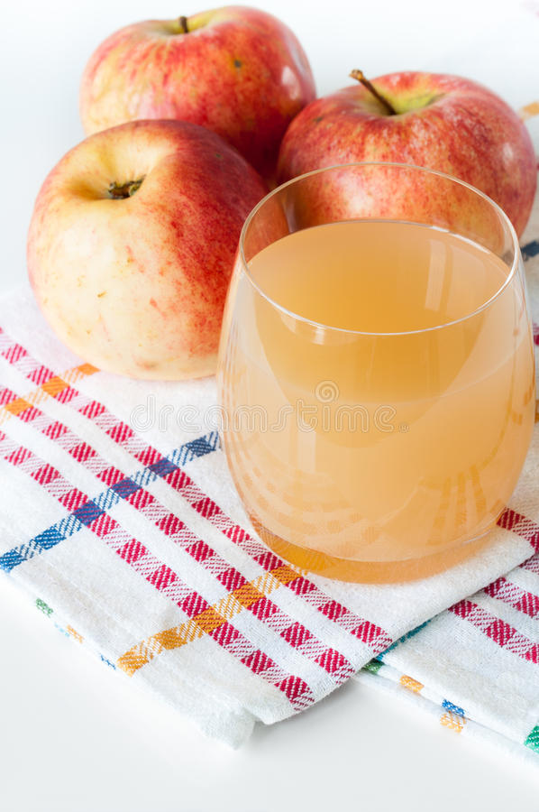 Natural apple juice and fruits. Glass of natural apple juice and fresh fruits on a cloth royalty free stock photo