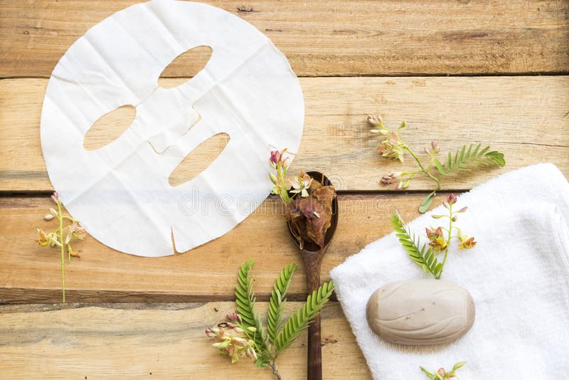 Natural aroma sheet mask extract herbal tamarind. Health care for skin face with flower tamarind ,leaf essence face mask arrangement flat lay style stock photo