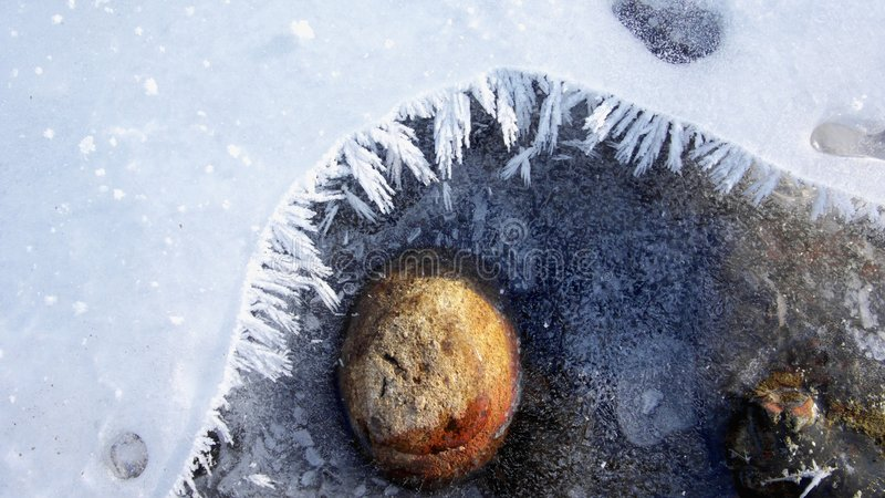 Natural Art. Red Stone inside a frozen River royalty free stock images