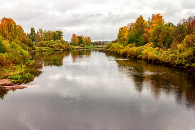 Natural autumn landscape with river shore scene and village view on fall background royalty free stock image