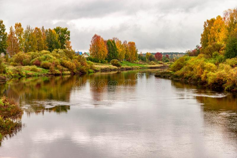 Natural autumn landscape with river shore scene and village view on fall background stock photos