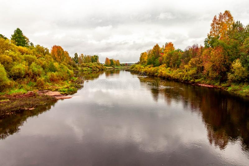 Natural autumn landscape with river shore scene and village view on fall background stock photo