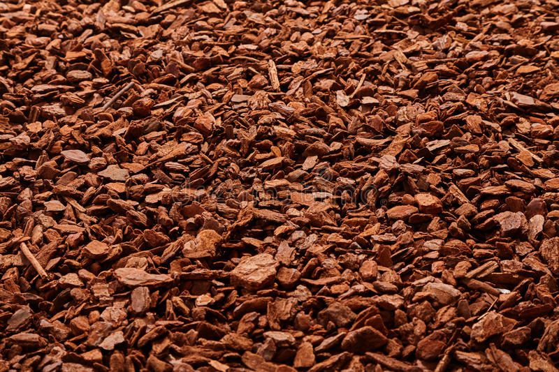 Natural background of angled view on mulch. Natural full frame background on angled view of red and brown pieces of tree bark mulch for gardening or natural stock photos