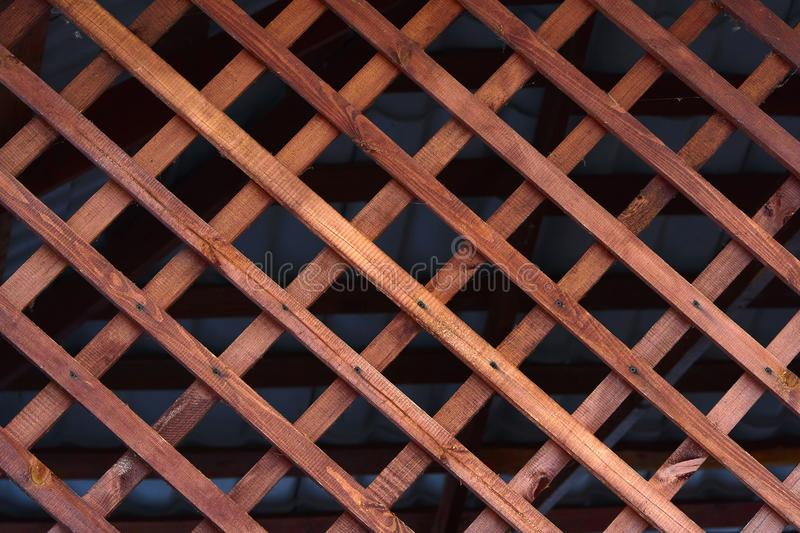 Natural background grille made of wooden slats. Element for the design of arbors, verandas and other wooden structures.  stock images
