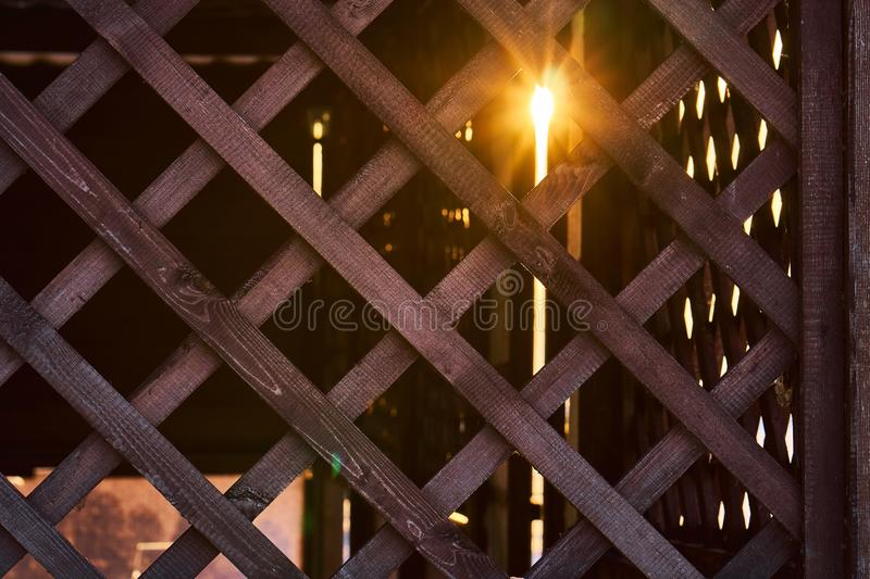 Natural background grille made of wooden slats. Element for the design of arbors, verandas and other wooden structures. The rays of the setting sun make their royalty free stock photography