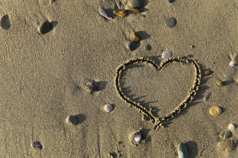 Natural background.Sand texture of sand with pebbles.Heart drawing on the sand. stock photography