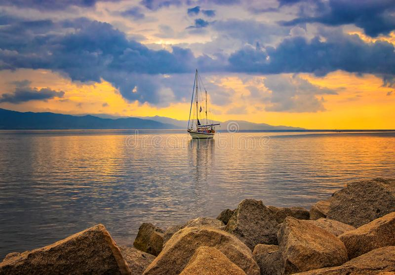 Natural background with Yacht in the Mediterranean sea at sunrise, Cagliari, Italy. he sun illuminates the island with beautiful. Golden colors. It is beautiful stock photo