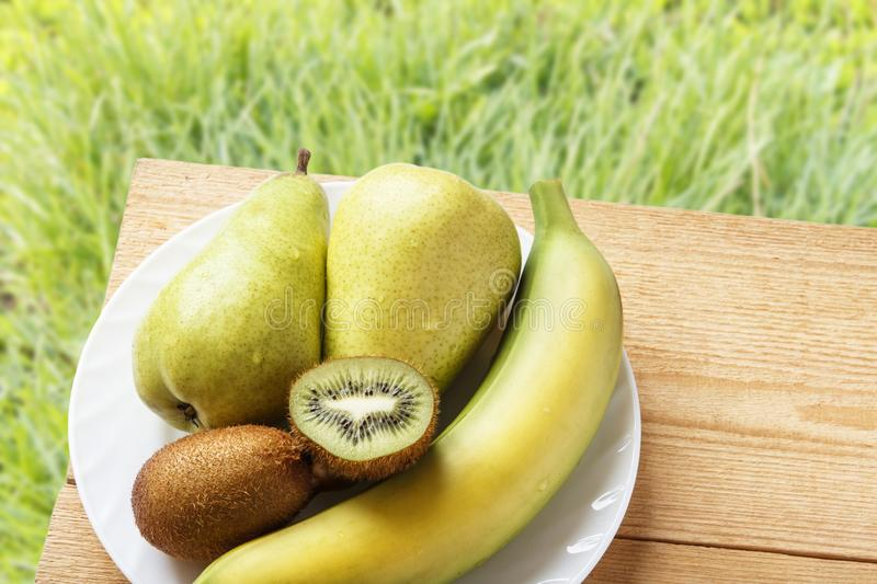 Natural banana, kiwi fruit and pears on wooden table and on green grasses background in nature . Top view with copy space. Rustic. Lifestyle concept stock photo