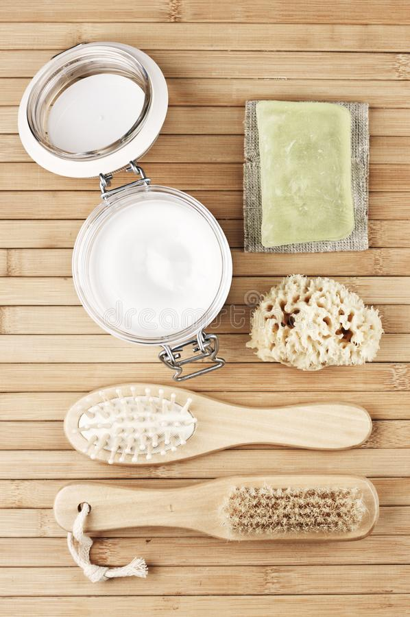 Natural bath accessories on wooden background: cosmetic cream, wood brushes, sponge and soap bar. SPA still life. Top view point, royalty free stock photos