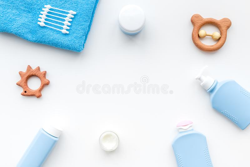 Natural bath cosmetics for kids. Bottles, towel and toys on white background top view copyspace stock photo