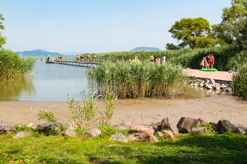 Natural beach with bathers walking on pier. At Lake Balaton, Hungary royalty free stock images