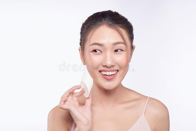 Natural beautiful woman with powder puff on white background.  royalty free stock images