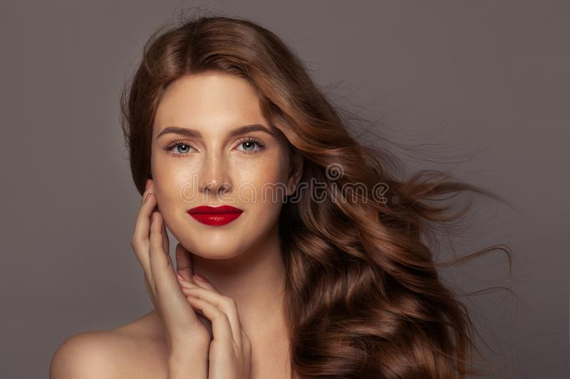 Natural beauty. Authentic redhead woman with blowing curly hair and red lips makeup, perfect face.  royalty free stock photography