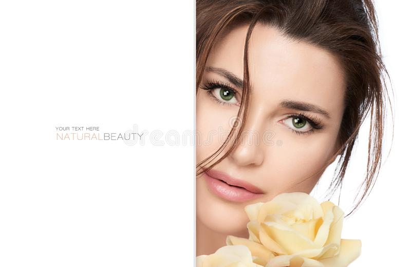 Natural beauty and bio cosmetics concept. With a gorgeous green eyed woman wearing subtle makeup with a flawless skin holding a  yellow rose to her face in a royalty free stock photography