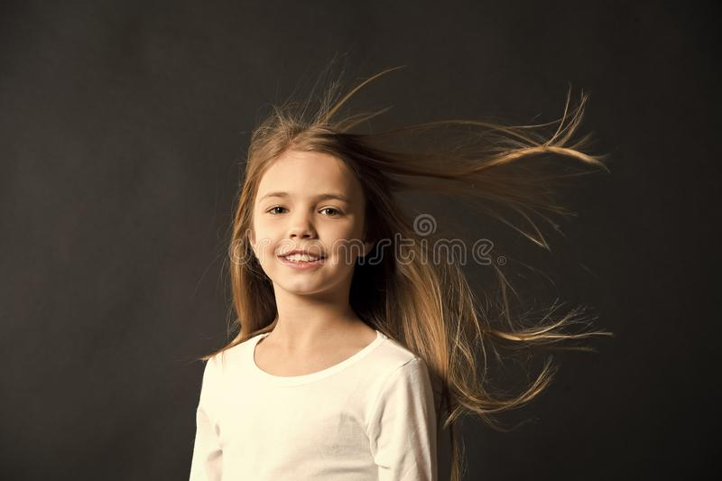 Natural beauty. Girl kid long hair flying in air, black background. Child with natural beautiful healthy hair. Quick royalty free stock images