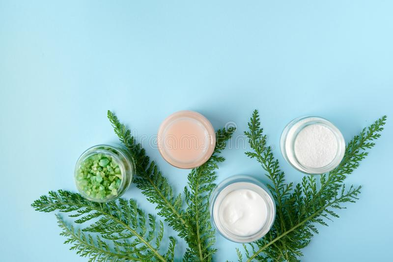 Natural beauty product concept for or bathroom. cream, soap,green leaves, sea solt on blue background with copy space. body skin royalty free stock photo