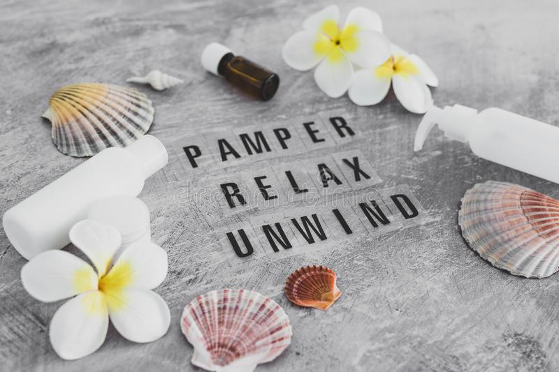 Natural beauty products, lotions and essential oil bottles surrounded by flowers and shells with Pamper Relax Unwind text. Natural beauty products conceptual royalty free stock photography