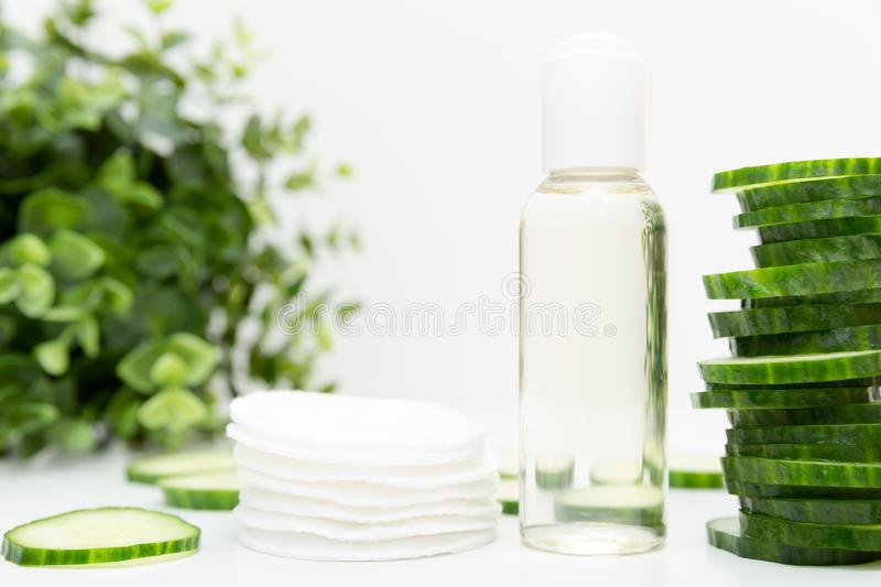 Natural beauty remedy. Liquid skincare cosmetic in bottle, green cucumber slice, morning facial fresh cleanser tonic. In natural light royalty free stock image