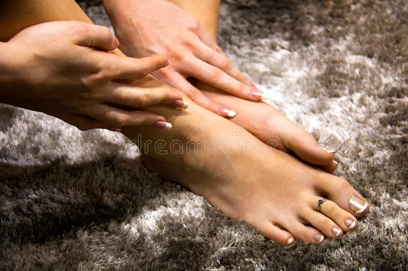 Beautiful woman feet and hands touching the soft skin, pampering foot and hand care, luxury french manicure and pedicure on nails. Natural beauty woman feet self royalty free stock images