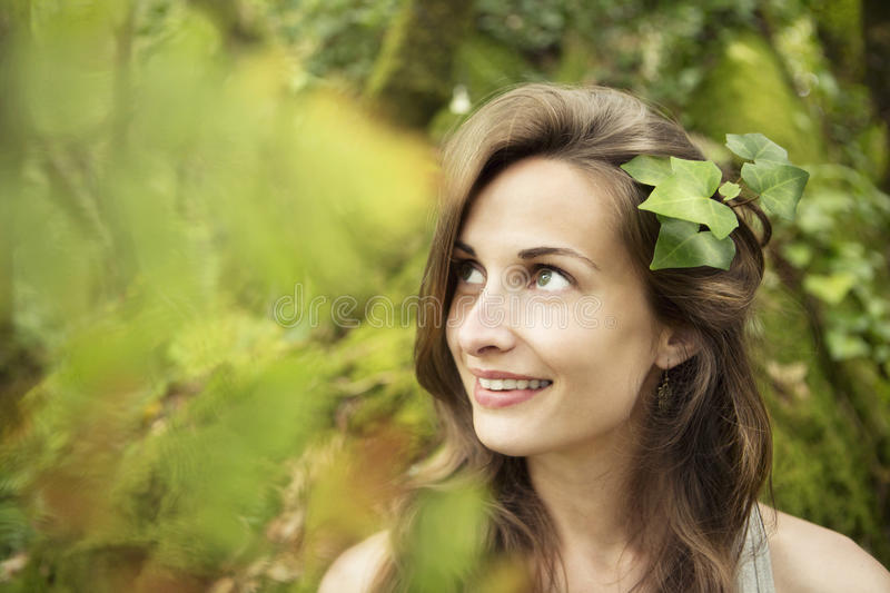 Natural beauty. Young beautiful girl with leaves in her hair smiling and looking away in a green fresh forest. Portrait. horizontal stock photography
