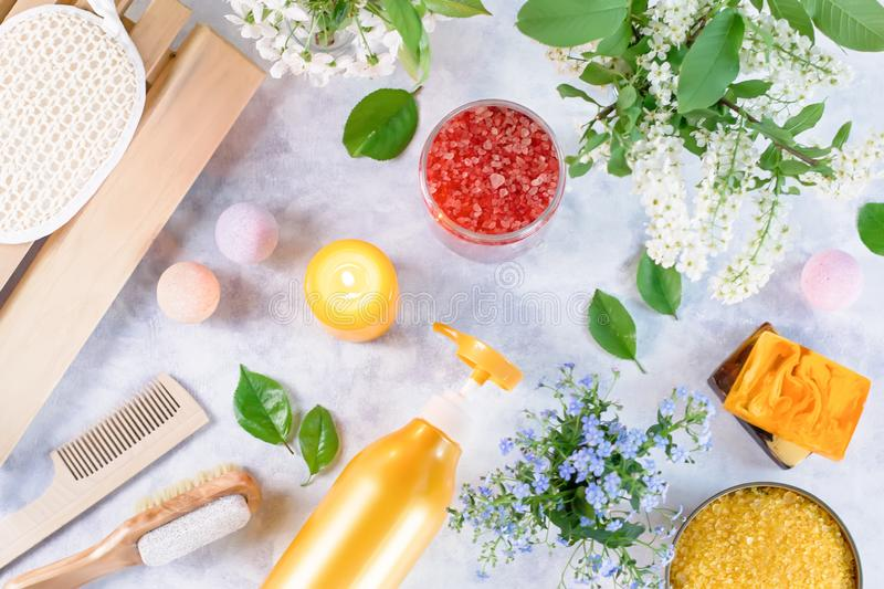 Natural body care products and accessories lay out with flowers and leaves. Eco friendly spa, beauty cosmetics concept. With copy space royalty free stock photo
