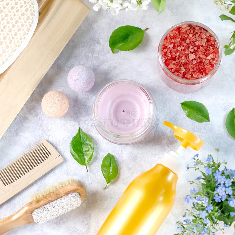 Natural body care products and accessories lay out with flowers and leaves. Eco friendly spa, beauty cosmetics concept. With copy space royalty free stock images