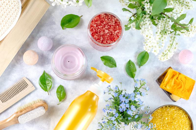 Natural body care products and accessories lay out with flowers and leaves. Eco friendly spa, beauty cosmetics concept. With copy space royalty free stock photos