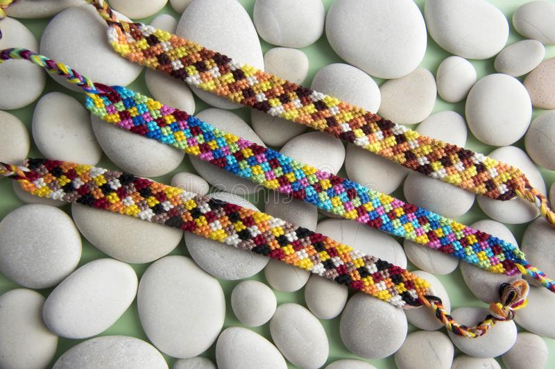 Natural bracelets of friendship in a row, colorful woven friendship bracelets, snow background, rainbow colors, checkered pattern royalty free stock photo